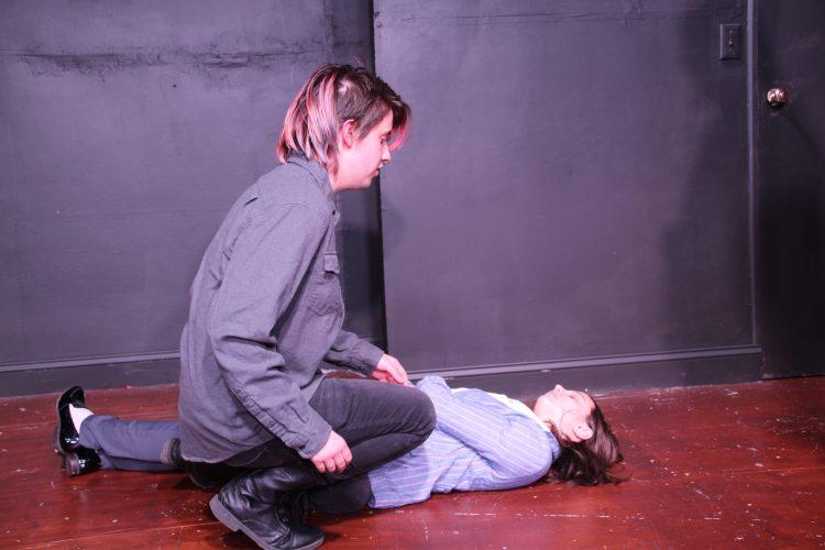 Hamlet (Jimmy Coblin) reveals the body of Polonius (Meghan Barnard).