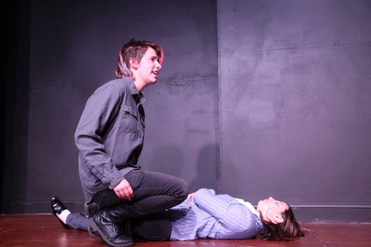 Hamlet (Jimmy Coblin) reacts to the body of Polonius (Meghan Barnard).